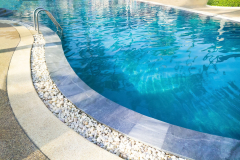 Swimming pool with metal ladder..Fragment of kidney-shaped swimming pool with stair. Cleaning blue color water. Сlose up in blur.