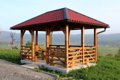 Newly built wooden gazebo structure with new roof mounted on concrete foundation with wooden table and chairs overlooking houses and fields in distance